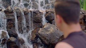 Avslappnande near vattenfall för man wrist för watch för avkoppling för begreppshandfack Closeupen av mans huvudet lager videofilmer