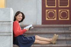 Avslappnande och läs- tra för härlig mer ung asiatisk resande kvinna Royaltyfria Foton