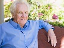 avslappnande pensionär för home manstående arkivbilder
