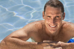 avslappnande simning för åldrig stilig manmedelpöl Royaltyfri Fotografi