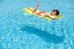avslappnande simningkvinna för pöl Arkivfoton