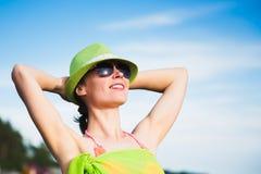 Avslappnande strandkvinna som tycker om sommarsolen Arkivfoto