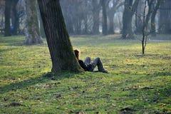 Avslappnande utomhus- i gräs Arkivfoto