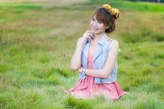 Avslappnande utomhus- sammanträde för nätt blond flicka i grönt gräs Royaltyfria Bilder
