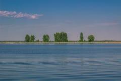 Avslappnande vattenlandskap med trädreflexioner i sjön Arkivbild