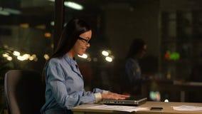 Avslutande arbete för ung kvinna på bärbara datorn och lämnakontor, avbrottstid, slut av dagen arkivfilmer