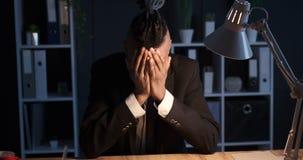 Avslutande kontorsarbete för trött affärsman på bärbara datorn sent på natten stock video