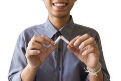 Avslutat röka, människa räcker avbrott av cigaretten som ler Royaltyfri Fotografi