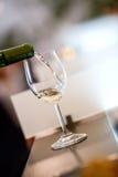 Avsmakning-vit vin häller in ett exponeringsglas arkivfoto