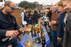 Avsmakningjänta med folkmassan av folk som dricker vin med bartendern på festivalen av Georgia Arkivfoton