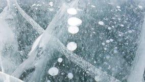 Avsnitt av det djupfrysta Laket Baikal Bubblor av olika format och djupa sprickor kan ses på djupet Härlig ljus is royaltyfria foton