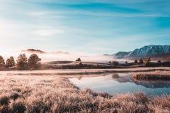 Avspegla yttersida av sjön i bergdalen Arkivfoto