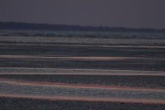 Avståndet kollapsade av den långa linsen som lämnar öppningsvattnet definierat av resningsolens röda färg Arkivfoton