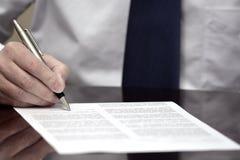 Avtal för affär för band för skjorta för avtal för man undertecknande pappers- vitt arkivfoto