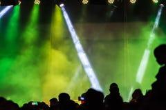 Avtala folkmassan som deltar i en konsert, folk som konturer är synliga, backlit av etappklartecken Smart telefoner är synlig här Arkivbild