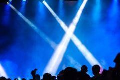 Avtala folkmassan som deltar i en konsert, folk som konturer är synliga, backlit av etappljus Lyftta händer och ilar telefoner är Arkivfoto