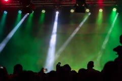 Avtala folkmassan som deltar i en konsert, folk som konturer är synliga, backlit av etappljus Lyftta händer och ilar telefoner är Royaltyfri Bild