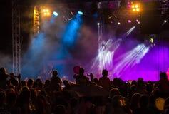 Avtala folkmassan som deltar i en konsert, folk som konturer är synliga, backlit av etappljus Lyftta händer och ilar telefoner är Fotografering för Bildbyråer