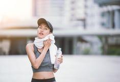 Avtorking av den svettades törstiga kvinnliga joggeren som dricker sötvatten Royaltyfri Bild