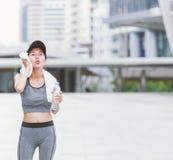 Avtorking av den svettades törstiga kvinnliga joggeren som dricker sötvatten, når utbildning Royaltyfri Fotografi