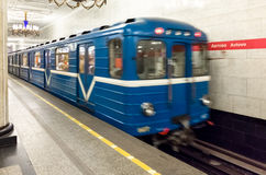 Avtovo Metro Station. Blue Saint Petersburg, Russia Metro train leaving Avtovo station with white marble walls and chandeliers Stock Image