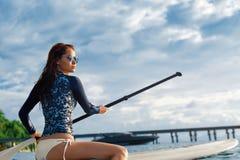 Avventura di viaggio Donna che rema sul bordo praticante il surfing Fotografie Stock