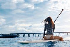 Avventura di viaggio Donna che rema sul bordo praticante il surfing Fotografia Stock