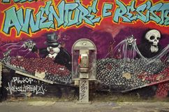Avventure e resistente. Milan, Italy - October 2, 2015: Public phone in front of a graffiti on the Via Festa Del Perdono in the city center Stock Photos