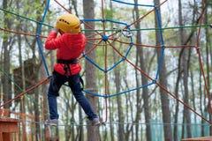 Avventuri il parco rampicante dell'alto cavo - la gente sul corso in casco della montagna ed attrezzatura di sicurezza Fotografie Stock