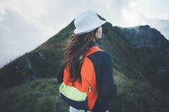 Avventuri la donna con lo zaino ed il cappello bianco che esaminano le montagne nuvolose Fotografia Stock Libera da Diritti