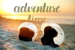 Avventuri le parole dell'iscrizione di tempo sul fondo della foto con due caschi bianchi sul tramonto della spiaggia Concetto di  Immagini Stock