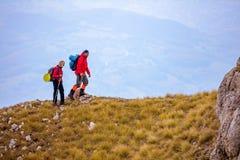 Avventuri, viaggi, turismo, aumento e concetto della gente - coppia sorridente che cammina con gli zainhi all'aperto Fotografie Stock Libere da Diritti