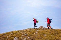 Avventuri, viaggi, turismo, aumento e concetto della gente - coppia sorridente che cammina con gli zainhi all'aperto Fotografia Stock Libera da Diritti