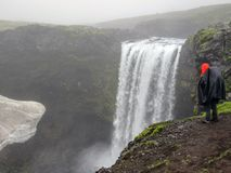 Avventuriere adulto maschio della viandante che fa un'escursione in impermeabile indietro che sta all'aperto esaminando cascata n fotografia stock