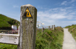 Avvertimento giallo della segnaletica di sicurezza del triangolo della scogliera instabile pericolosa Immagine Stock