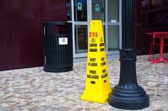 Avvertimento giallo dello slittamento sul cono bagnato del pavimento fotografie stock