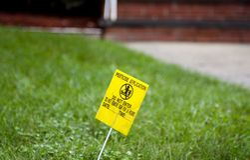 Avvertimento giallo di applicazione dell'antiparassitario sul prato inglese verde Fotografie Stock