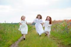 Avvicinamento funzionato tre ragazze Bambini che giocano all'aria fresca Fotografia Stock