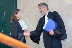 Avvocati che stringono le mani che finiscono su di incontrarsi immagini stock