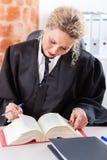 Avvocato in libro di legge della lettura dell'ufficio Immagini Stock