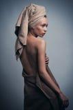 Avvolto in asciugamano sopra fondo grigio Fotografie Stock