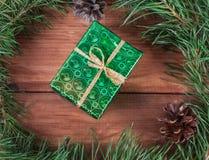 Avvolto in contenitore di regalo del Libro Verde nell'albero di Natale verde si ramifica ed i coni Immagine tonificata Fotografia Stock