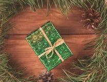 Avvolto in contenitore di regalo del Libro Verde nell'albero di Natale verde si ramifica ed i coni Immagine tonificata Fotografia Stock Libera da Diritti