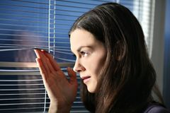 Await. Young woman is peeking out through the window Stock Photos