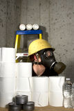 Awaiting Disaster. Woman dressed in gas mask and hard hat hiding in the basement with stockpiled goods Royalty Free Stock Photography