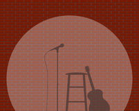 Awaiting Musician. A Brick Wall With Spotlight on guitar, stool and microphone Background Stock Photos