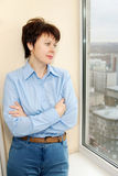 Awaiting woman wears a blue shirt stands next to a window Stock Image