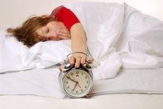 Awake. Awaking boy turns off the alarm clock Royalty Free Stock Images