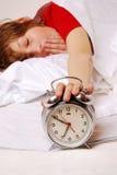 Awake. Awaking boy turns off the alarm clock Royalty Free Stock Photos