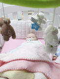 Awake baby boy lying in white cot with mobile Stock Photo